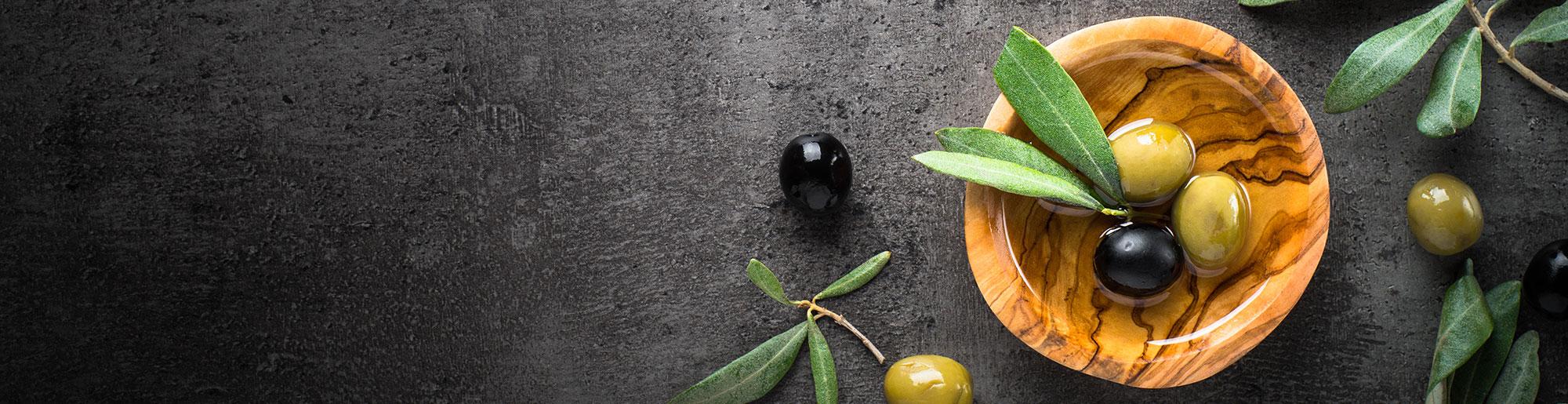 Grüne und schwarze Oliven in einer Holzschale